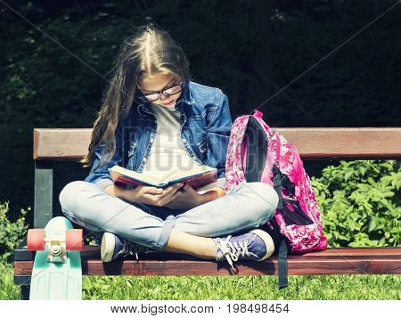 Beautiful blonde teen girl in jeans shirt reading a book on the bench with a backpack and skateboard in the park on a sunny summer day.