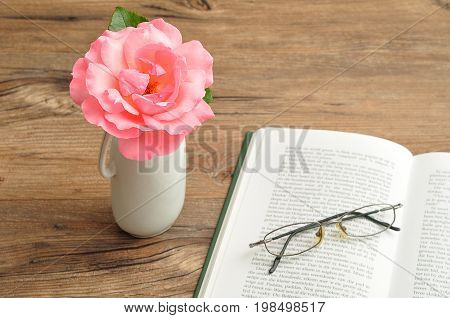 A single pink rose in a vase with a reading book and spectacles