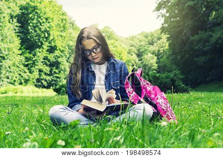 Beautiful blonde schoolgirl girl in jeans shirt reading a book on grass with a backpack in the park on a sunny summer day