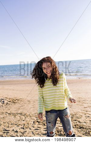 Laughing young woman have fun and listening to music on beach on background of sea. Curly girl dancing with earphones and phone outdoor