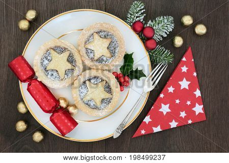 Christmas mince pie tarts on a plate with sliver fork, napkin and cracker with bauble decorations and foil wrapped chocolates on oak background.