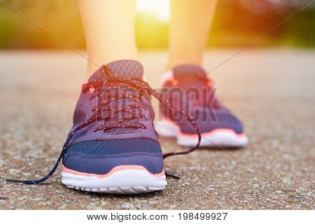 Legs In Sports Running Shoes With Untied Laces On The Road While Jogging. Concept Of Sports Lifestyl