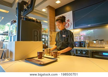 SHENZHEN, CHINA - CIRCA OCTOBER, 2015: young pretty barista at McCafe preparing coffee. McCafe is a coffee house style food and drink chain, owned by McDonald's.