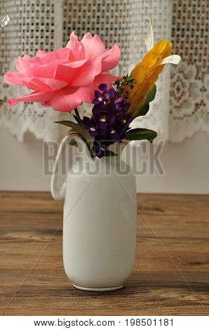 Variety of colorful flowers displayed in a white vase
