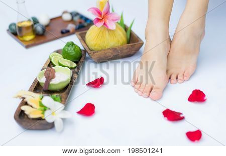 Spa treatment and product for feet spa with flowers and water wooden background; select and soft focus.