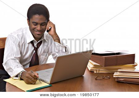 Handsome African-American businessman working on a laptop and talking on cell phone