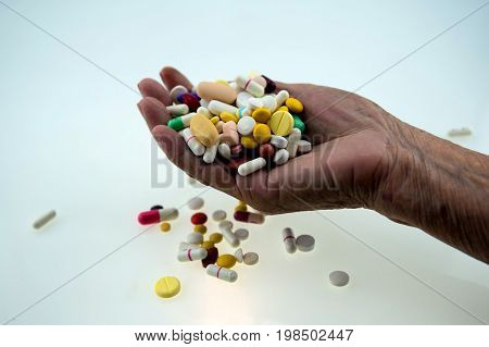 Many multi-colored pills in a Senior's hands on white background; Alzheimer's patients; caring for the health of the elderly patients