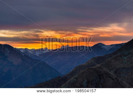 Colorful Sunlight Behind Majestic Mountain Peaks Of The Italian - French Alps, Viewed From Distant.