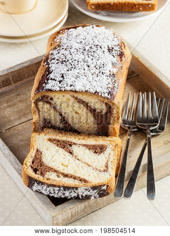 Vanilla and chocolate marble cake with a slice cut off.
