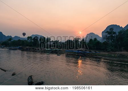 The colorful sunset over Nam Song River with hot air ballon in Vang Vieng Laos.