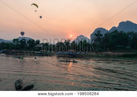 Wide angle picture of sunset over Nam Song River with hot air ballon and tourists on the boat in Vang Vieng Laos.