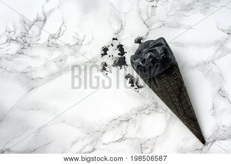 Black ice cream on marble table. Top view. Black and white concept. Sweet dessert made from the goth cone and dark topping.