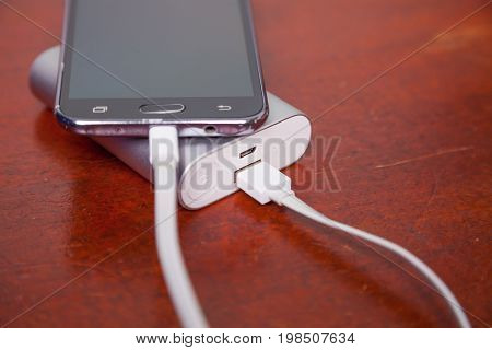 Mobile Call Phone Charging With Power Bank on wooden table