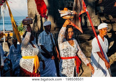 BALI INDONESIA - MARCH 07: Balinese people in traditional clothes take part in the ceremonial procession during Balinese New Year celebrations.