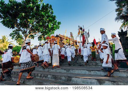 BALI INDONESIA - MARCH 07: Balinese people in traditional clothes carry jempana or wooden litter at the procession during Balinese New Year celebrations.
