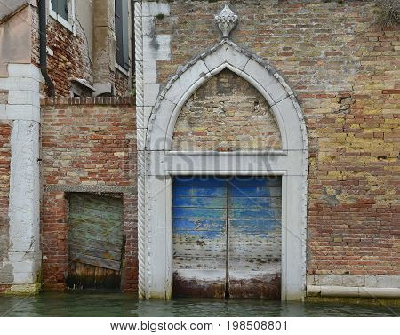 An old wooden door in a derelict building opening onto a canal in the Dorsoduro quarter of Venice