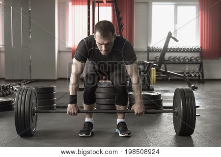 Young Man Doing Deadlift Exercise At Gym.