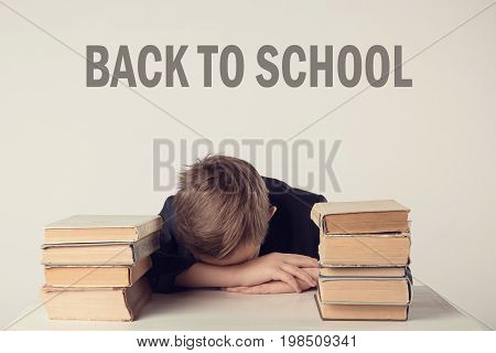 Pupil In Suit At His Desk On Grey Background With Books. Boy Fell Asleep During Homework. Inscriptio