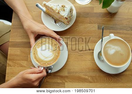 Cup Of Coffee In A Cafe And A Girl's Hands. Close-up Of Woman's Hands, Sitting With Cup Of Coffee In