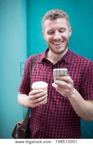 Man Standing In Front Of Blue Door Reading Text Message