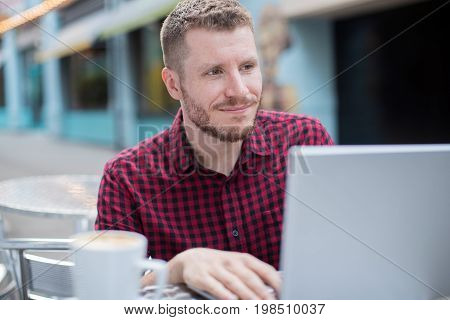 Young Man At Outdoor Cafe Working On Laptop