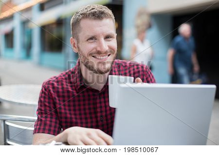 Portrait Of Young Man At Outdoor Cafe Working On Laptop