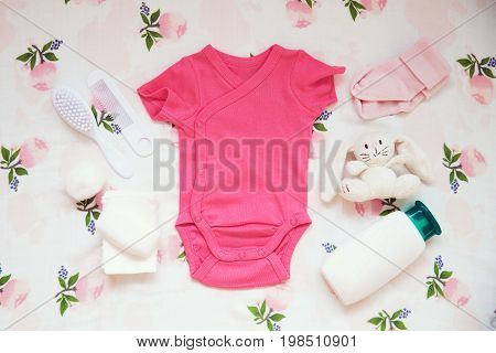 Baby clothes and necessities on light fabric background. Gentle soft and cozy mood. Newborn background with copy space.