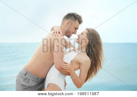 Happy couple cuddling on seashore