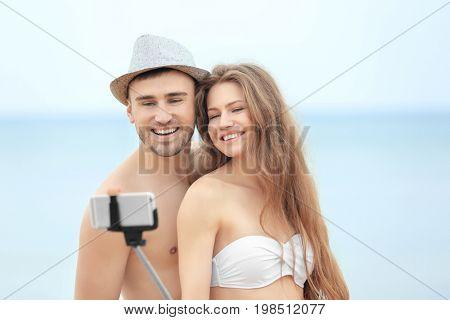 Happy couple taking selfie on beach