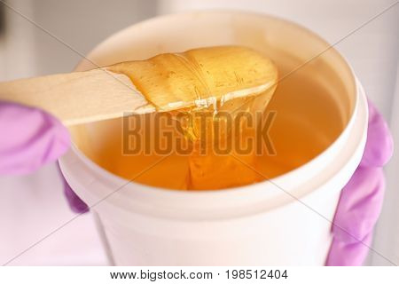 Hands of beautician holding plastic bucket with sugaring paste and wooden stick, closeup. Epilation concept