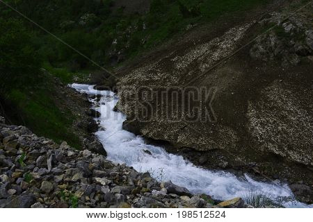 rapid mountain river flowing between steep cliffs