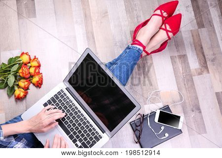 Young woman in stylish flat shoes with laptop sitting on floor