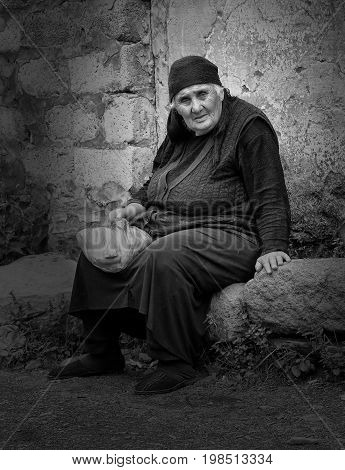 SNO, GEORGIA - JULY 1, 2014: Old woman sitting on a stone in a Caucasian village on July 1, 2014 in Georgia, Europe
