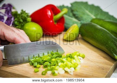 Food prep chopping fresh healthy green onions colorful vegetables produce cutting board knife on white background