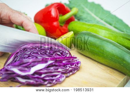 Food prep chopping fresh healthy colorful red cabbage vegetables produce cutting board knife on white background