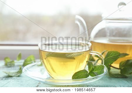 Cup of hot aromatic tea with lemon balm on window sill