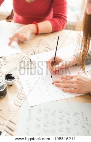 inspiration, patience, lettering concept. two women wearing grey and red sweatshirts creating various fonts with help of special equipment on the desk covered brown paper for sketching