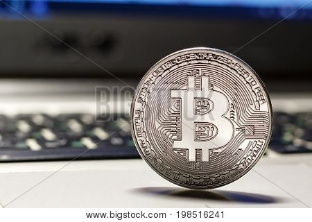 Silver Bitcoin On The Laptop Touchpad Closeup. Cryptocurrency Virtual Money