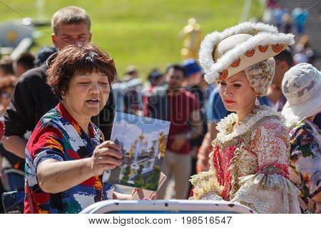 PETERHOF/ RUSSIA - JULY 2, 2017. Asian woman wants to be photographed with the model in an ancient court costume in the Peterhof park. Saint Petersbug, Russia.