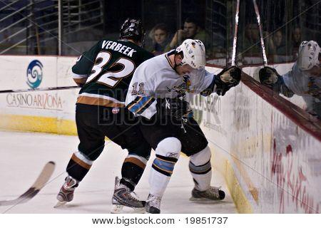 PHOENIX, AZ - DECEMBER 18: Utah Grizzlies wing Tim Verbeek (#32) checks Phoenix Roadrunners defenseman Matt Burke (#11) during the ECHL hockey game on December 18, 2008 in Phoenix, Arizona.