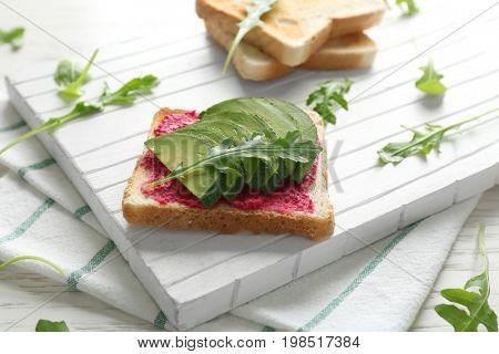 Delicious spicy toast with avocado and ruccola on white cutting board