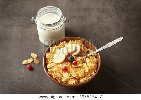 Cornflakes in bowl and jar with milk on gray table