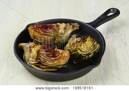 Artichokes in Cast Iron Skillet, the vegetables have been cooked on a grill and are served in pan