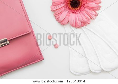 Woman health care, gynecology. Closeup of soft daily pads, birth control pills and pink bag on white background. Contraception and regular cycle, hormonal balance concept