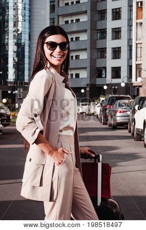 A beautiful woman walking around a city with her luggage