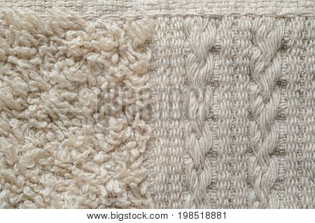 A macro shot of an element of beige color towel. Fleecy part and decorative element with braided pigtails. Texture is similar to the texture of a fleecy knotted-pile carpet.