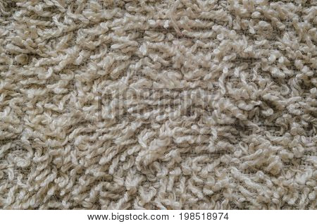 Macro shot of a beige color towel. Texture is similar to the texture of a fleecy knotted-pile carpet. Chaotic pattern of villi on fabric material.