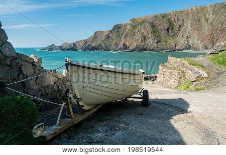 White wooden rowing boat ready to launch at pier at Hartland Quay in North Devon, England