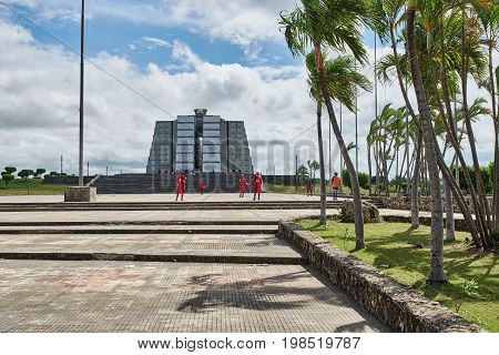 SANTO DOMINGO DOMINICAN REPUBLIC - MARCH 24 2017: Christopher Columbus Lighthouse (Faro a Colon ) monument in tribute to Christopher Columbus inaugurated in 1992. Young people are playing sports in front of the building.