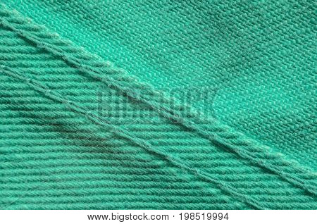 Green Denim Tissue Structure Textile Texture Close-up. Macro shot of the finishing seam on a green jeans product.